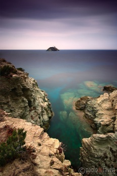 """The tiny Giraglia Isle with its lighthouse and Genovese watch tower stands out at sea in front of the rocky coast of the northern tip of the Cap Corse near to Barcaggio in Corsica, France. This wonderful part of the Corsica coast features countless spots like this, and it is easily accessible thanks to the """"sentier du douaniers"""", a track that links the village of Centuri to Macinaggio via Barcaggio, a path used in the past by the custom officers who surveyed the many small bays of the area. This picture was taken on a late afternoon of mid of September, and it's the result of 3 minutes of exposure obtained thanks to the use of a strong neutral filtration."""
