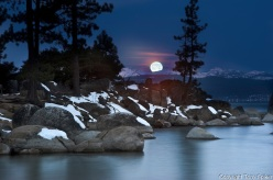 The moon sets over the Sierra Nevada Mountains and Lake Tahoe's Sand Harbor.